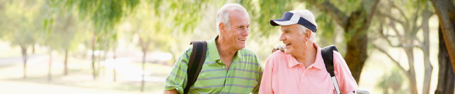 Two senior men walking and golfing