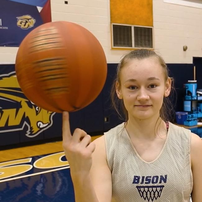 Female student spinning basketball on her index finger