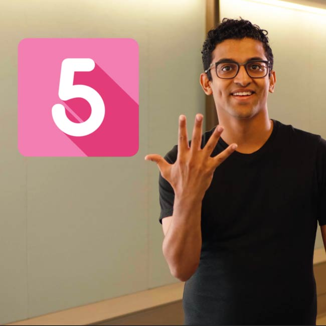 Man holding up number five with his hand in sign language