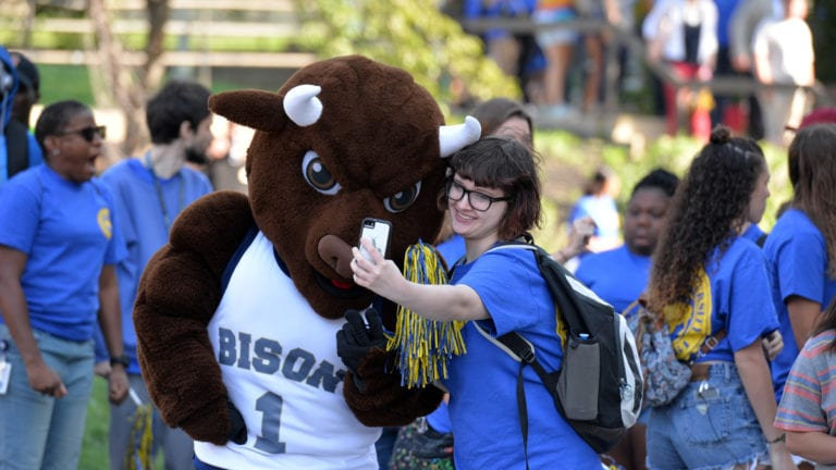 Student taking a self with Bison