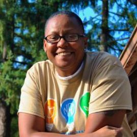 Stephanie is looking directly at the camera smiling with trees in the background. She is standing behind a wooden cabin-like canteen building while her arms are resting on the wooden railing. Stephanie is wearing the NAD YLC 2014 t-shirt [Beige colored t-shirt with a logo of three light blubs in upper chest area: left is orange with a white outline of a book, center is light blue with a white outline of NAD]