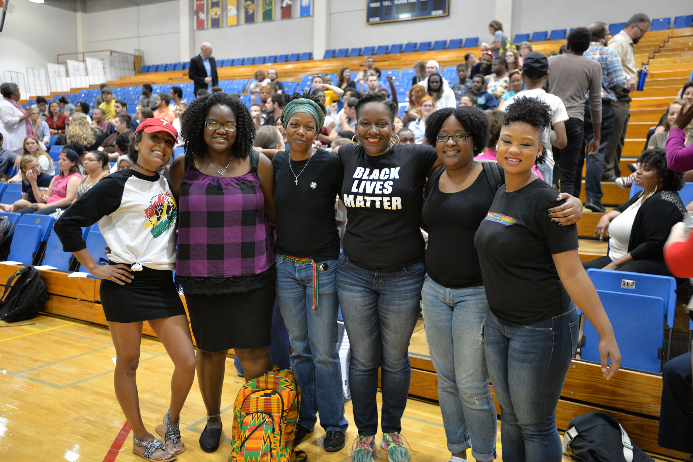 In front of blue-seated bleachers and brown steps, six women formed a u-shape hugging each other and smiling at the camera.