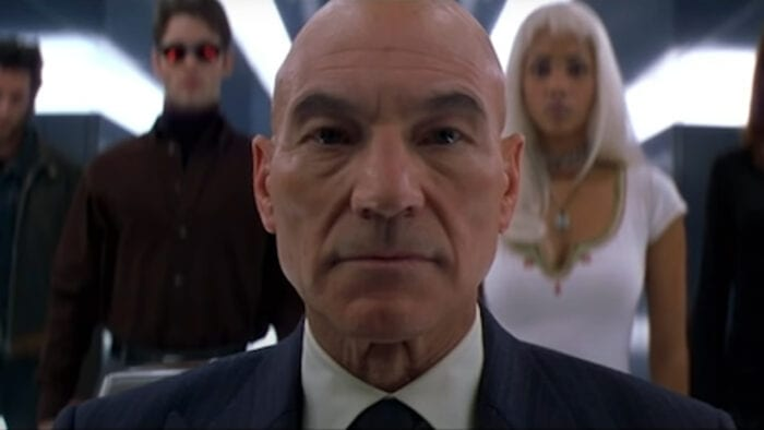 X-Men 2000 film showing Patrick Stewart as Charles Xavier with other X-Men in the background including Storm and Cyclops