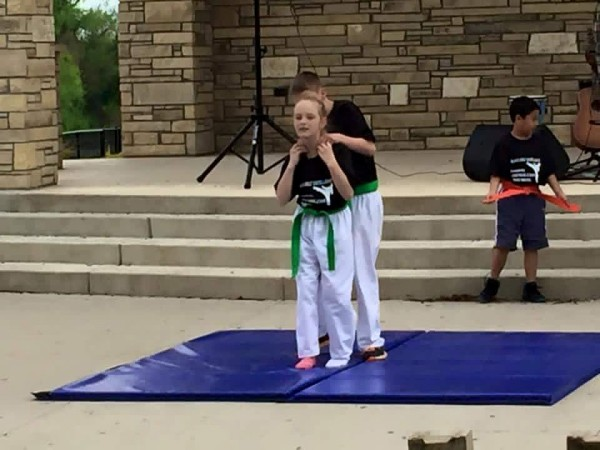 Karate Kid student being grabbed on throat from behind and showing self defense