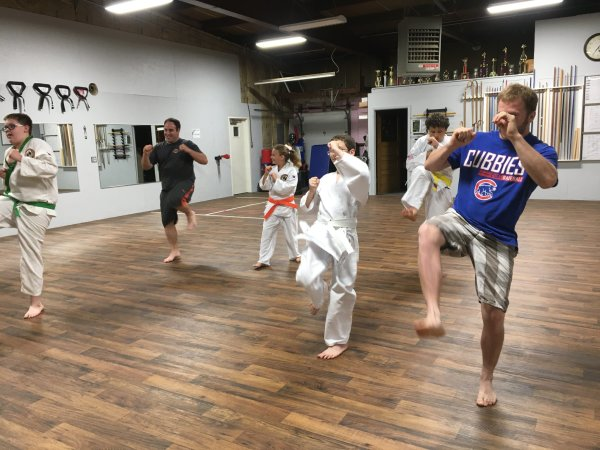 Students teaching their dads how to perform a front snap kick