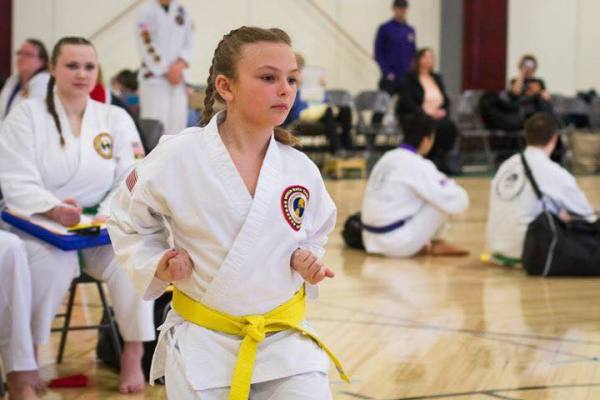 Karate Club Yellow Belt member concentrating hard while performing her form