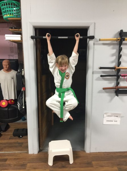 Green Belt Karate Girl hanging on bar with legs pulled up
