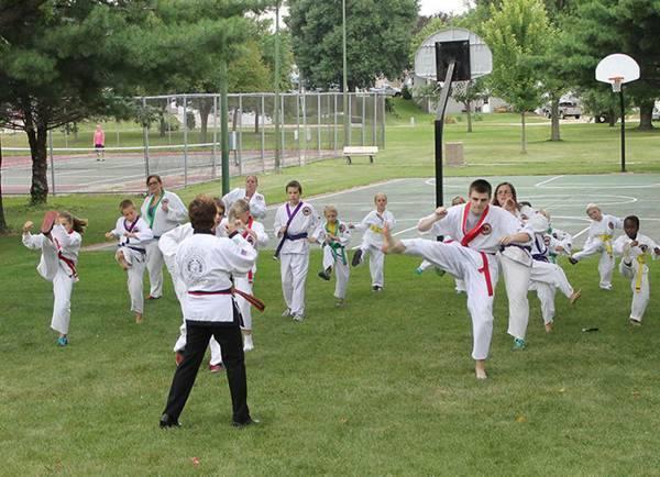 Class of Men, women, and children in park performing kicks for karate class