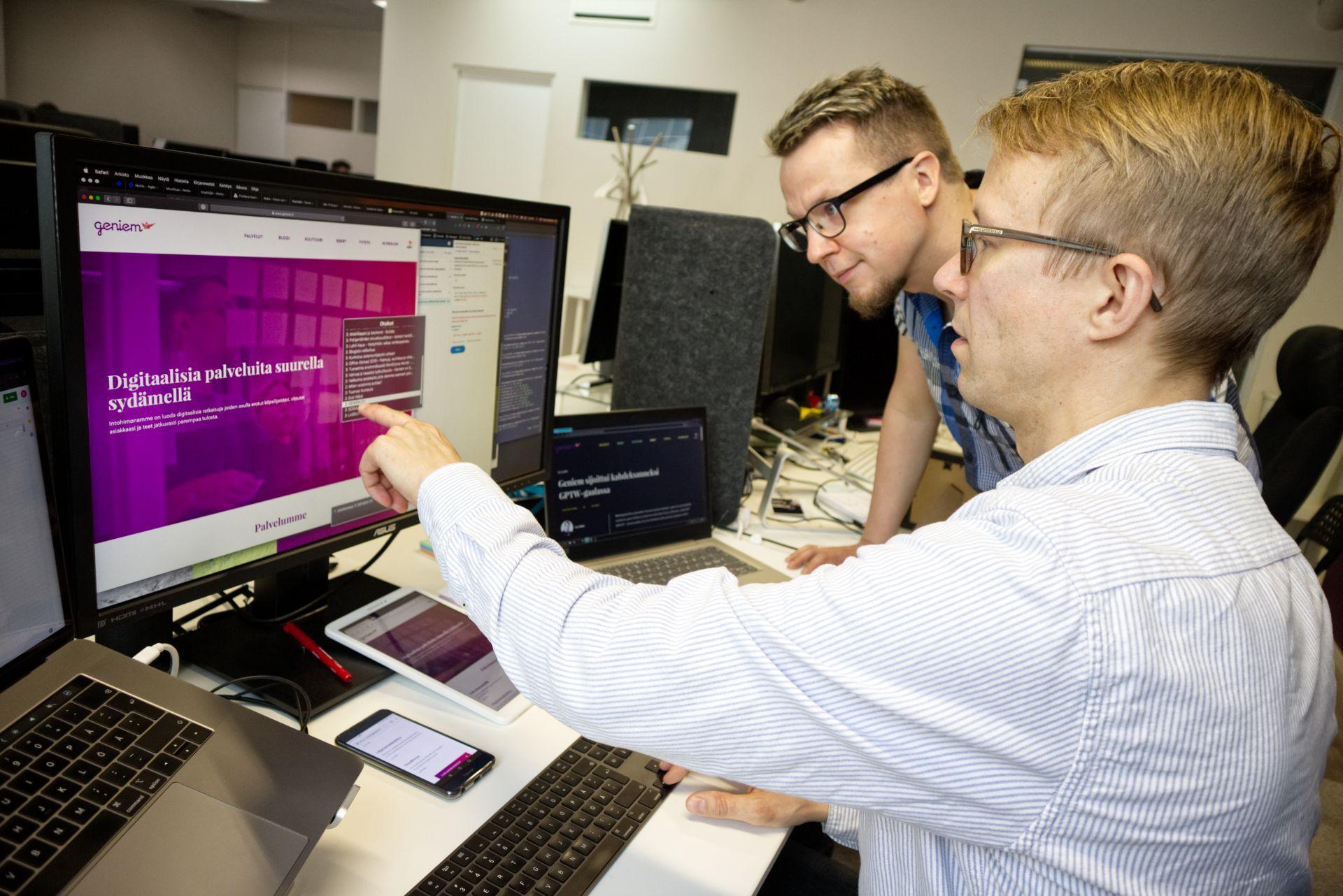 Mies osoittaa tietokoneruutua kolleegalleen