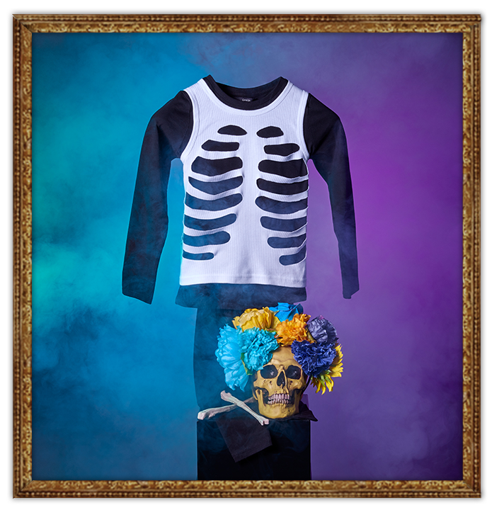 DIY George skeleton Halloween costume and yellow skull covered in flowers, all shrouded in smoke
