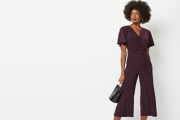 Woman wearing a purple jumpsuit holding a bag