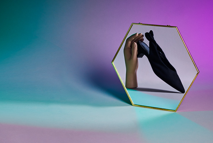 Hexagonal mirror with a mannequin hand holding a black shoe