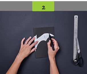 Placing stencil bat shape over black card