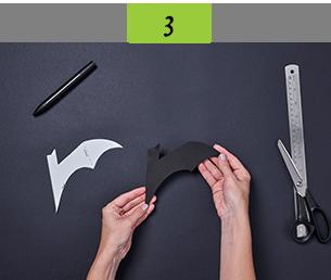Cutting bat shape out of black card using stencil
