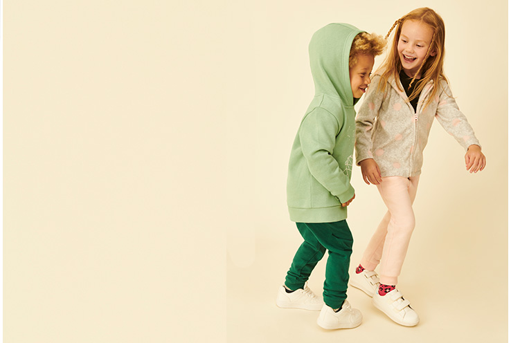 Two kids smiling, a boy in green joggers and a green hoodie, and a girl in pink joggers and a jacket