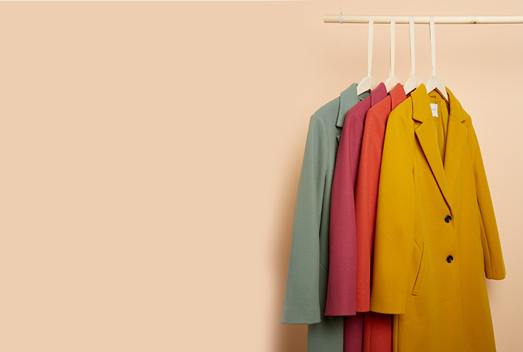 Four longline coats in green, pink, coral and yellow on hangers on a rail