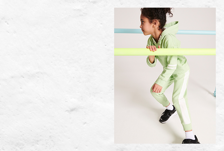 Child exercising in neon green tracksuit and black gym trainers