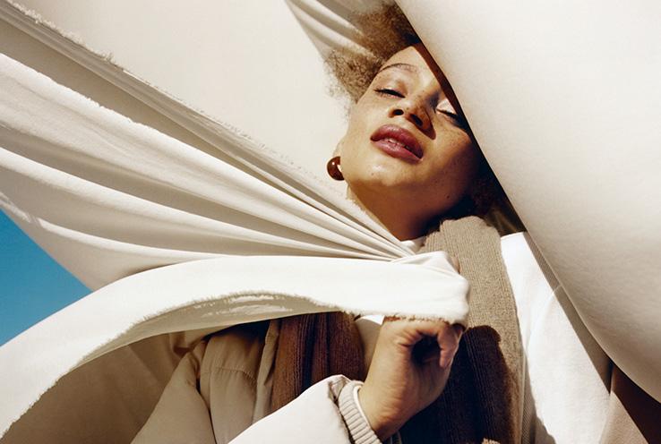 Woman in between beige sheet
