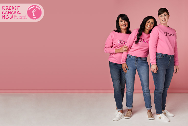 Three women wearing pink jumpers and blue jeans