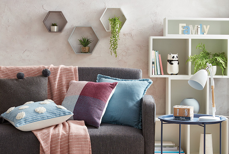 Shelves filled with artificial plants and accessories, a grey sofa with an assortment of cushions and a side table with a lamp