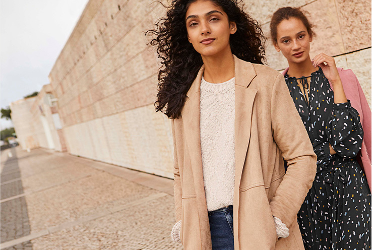 Two women outdoors, one wearing a camel suede effect longline trench coat over a cream jumper and jeans, the other wearing a pink coat over a printed dress