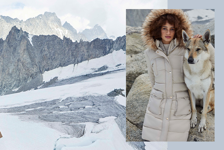 Woman in Winter Neutrals coat posing next to a dog on a mountainside
