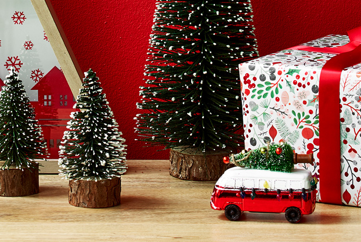 Christmas trees surrounded by a present and red van ornament