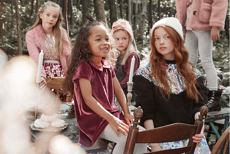 Children sitting and standing on a table in the woods