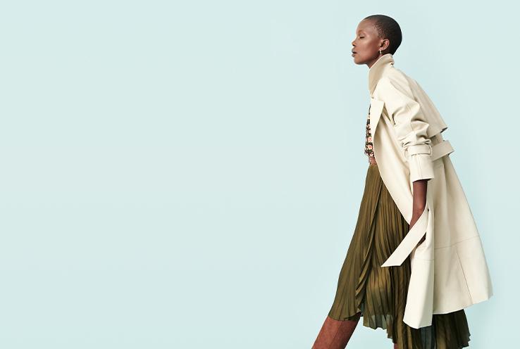 Woman in cream trench coat and khaki dress