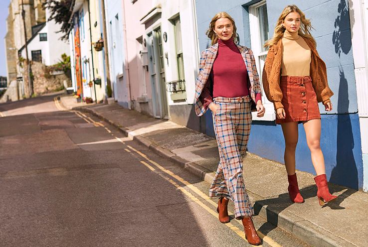 Two women walking down the street wearing George Heritage trend clothing
