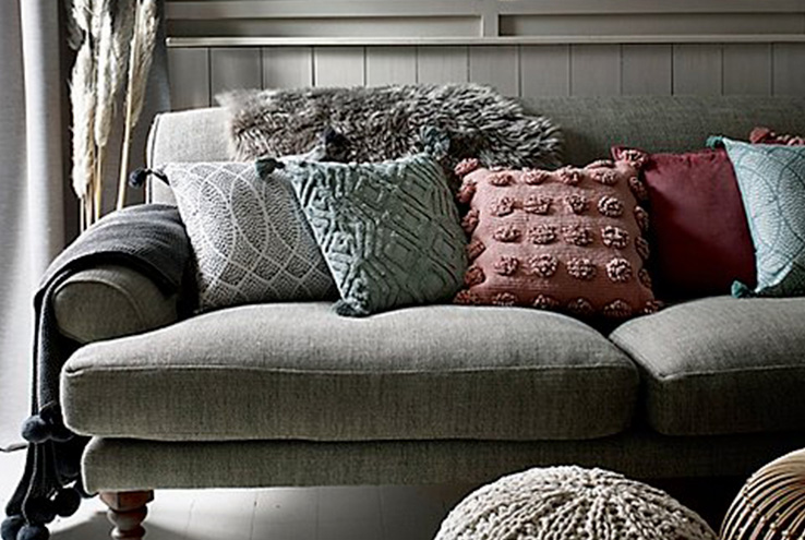 A variety of textured cushions on a sofa
