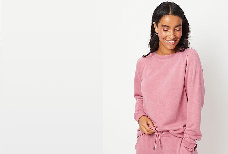 Woman wearing pink sweatshirt and matching joggers