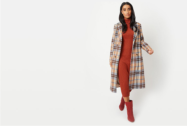 Woman wearing rust coloured roll neck dress, boots and a blue and beige check coat