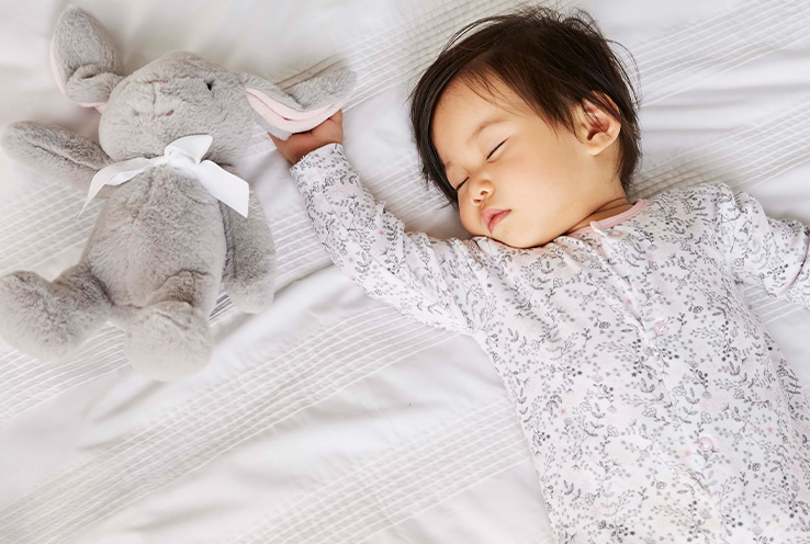Baby asleep on bed wearing floral print sleepsuit and clutching an elephant soft toy