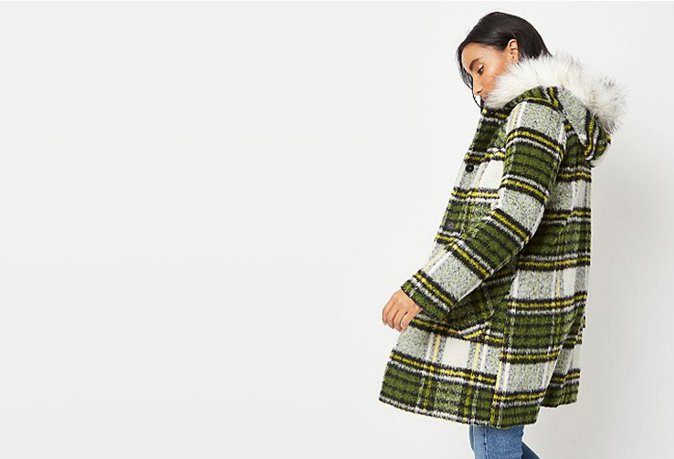Woman wearing a green checked coat with a faux fur hood