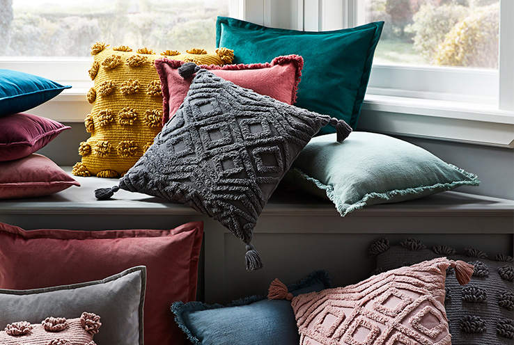 Colouful textured cushions by a windowsill