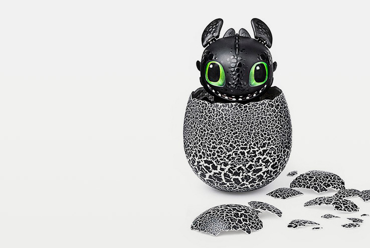 Black baby dragon with green eyes poking out from shell