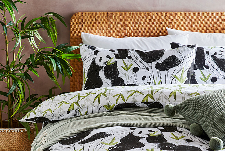 Double bed with bedding decorated with pandas, green cushions and matching throw and an artificial plant