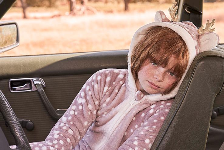 Girl in seat of car wearing pink hooded reindeer zip up dressing gown