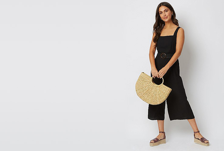 Channel a black culotte jumpsuit with a woven belt