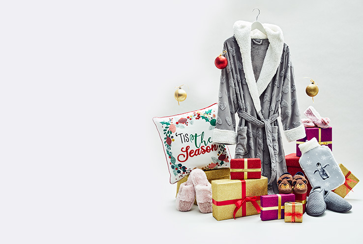 Grey robe on a hanger surrounded by presents, cushions, slippers and a hot water bottle