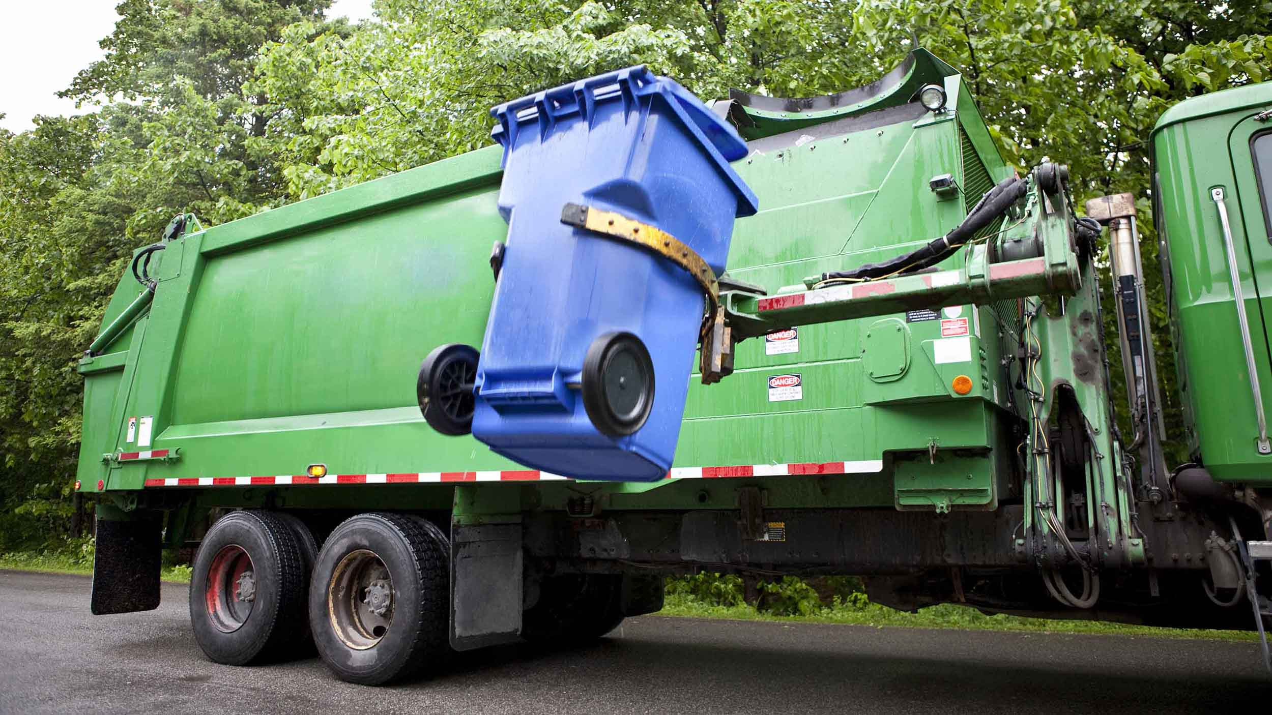 Green garbage truck lifting a blue dumpster