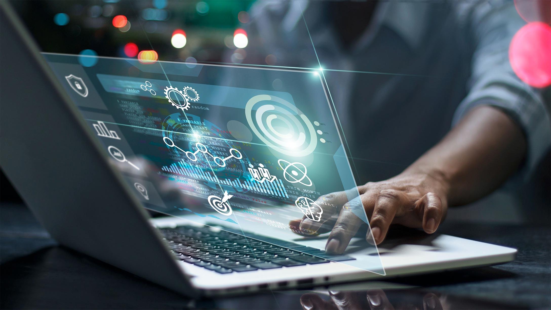 Imagen de un computador con información saliendo, y una mano de alguien operándolo