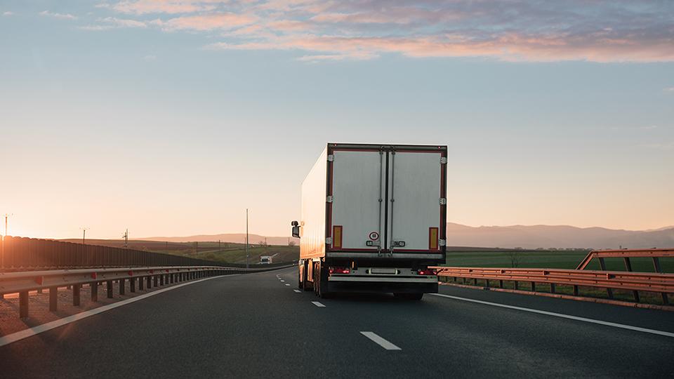 Bild eines Lkw, der auf einer Straße fährt.