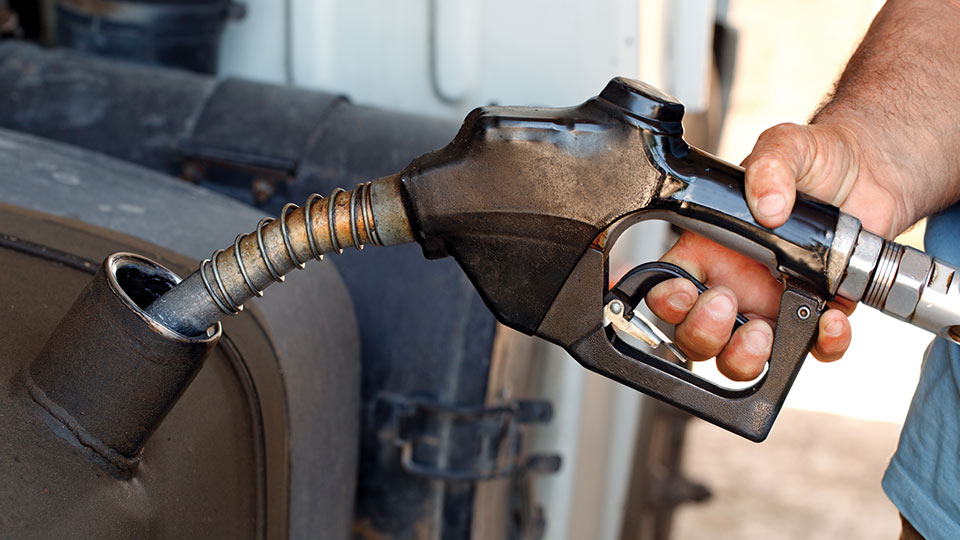 A hand holding a fuel nozzle to a vehicle's gas tank