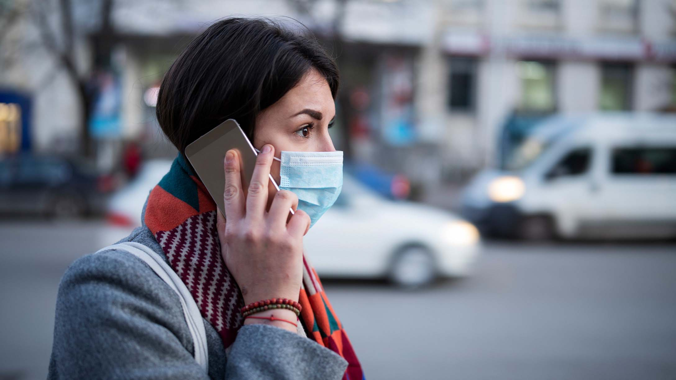 Woman in a mask on a cell phone
