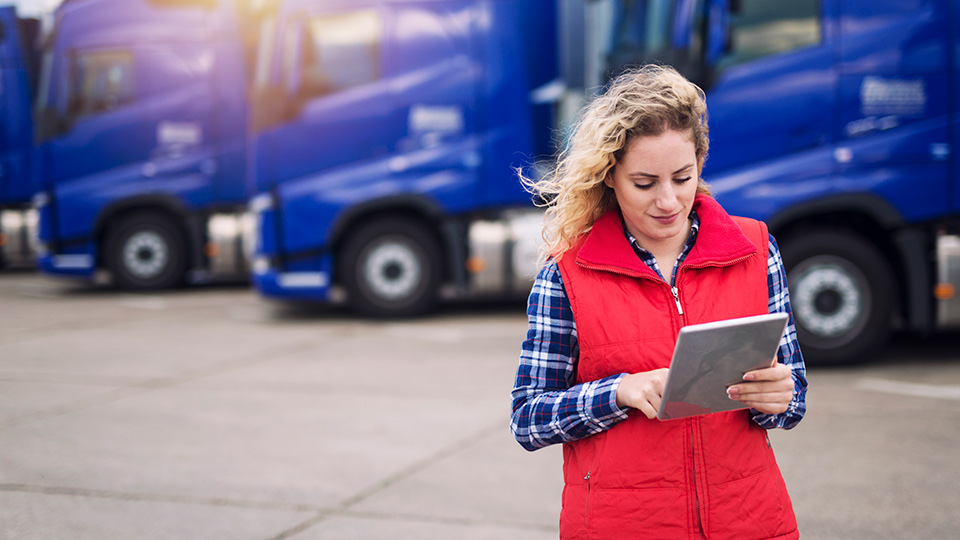 Woman in a red vest in front of blue trucks looking at a tablet reviewing unassigned yard moves
