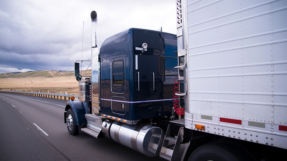 White and blue heavy duty truck on a freeway