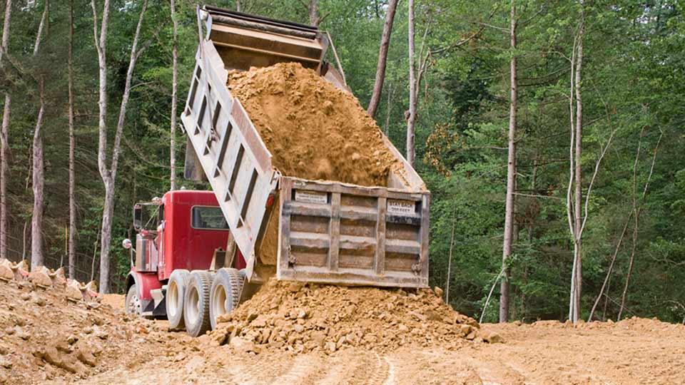 Dump truck dumping soil near a forest