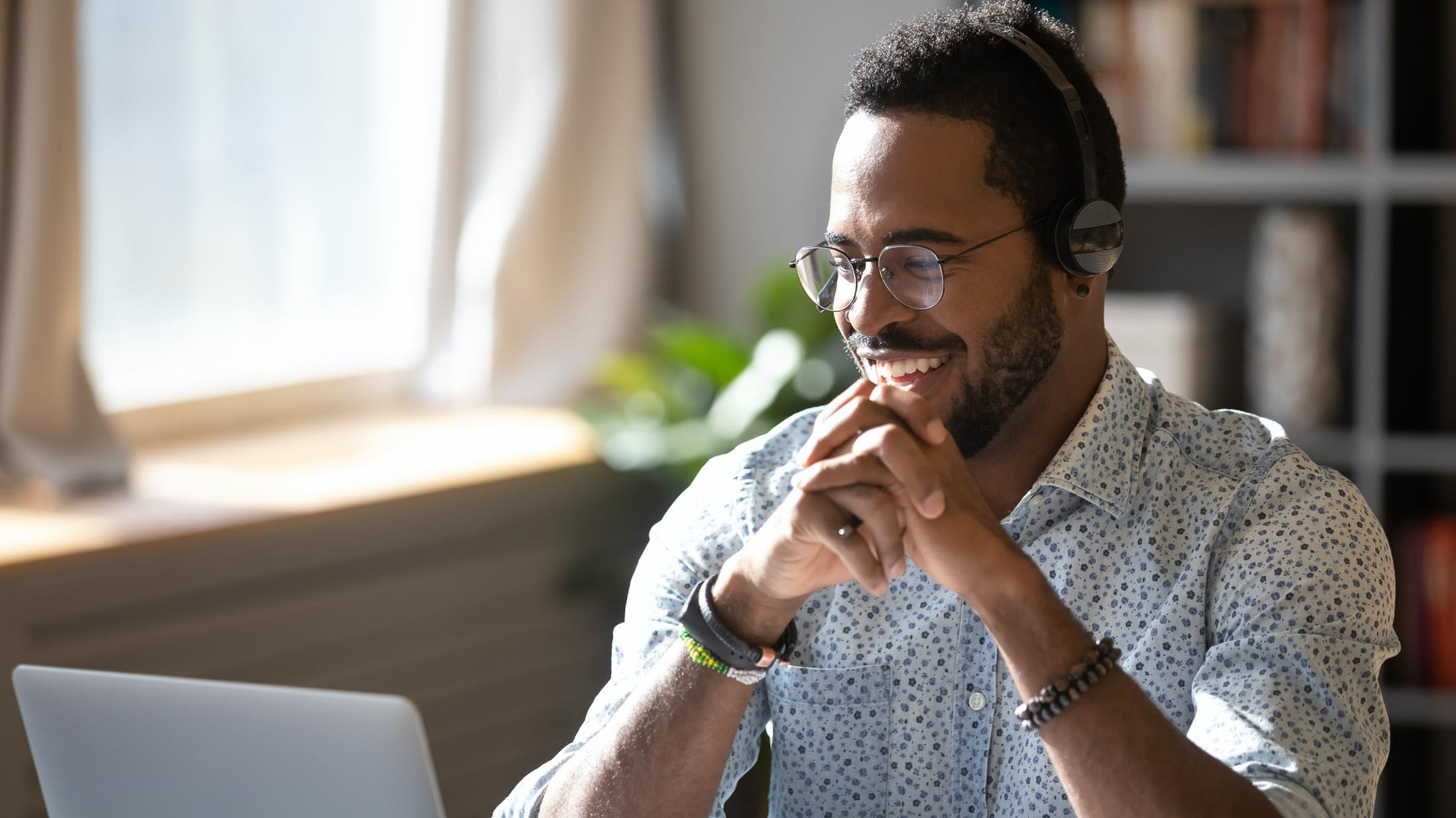 Man smiling in front of a laptop working remotely